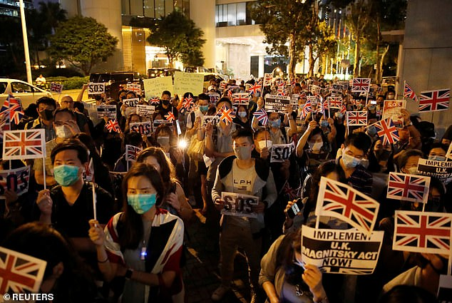 Hundreds of Hong Kong protesters chant 'God Save the Queen' and 'We are British' while forming a human chain around the British Consulate on October 23