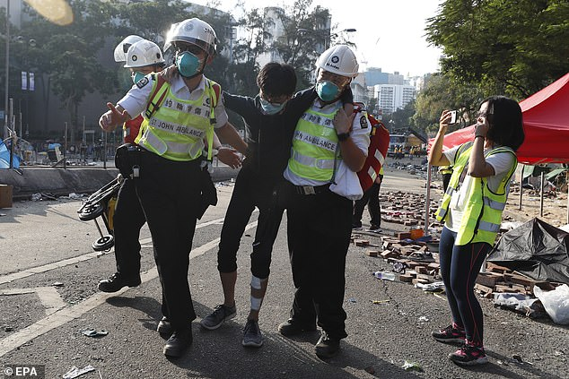 Hong Kong has been rocked by anti-government protests since the beginning of June and tensions surged from last week. Pictured, medical staff help a protester leave Hong Kong Polytechnic University yesterday, on the fourth day of a stand-off with police in Hong Kong