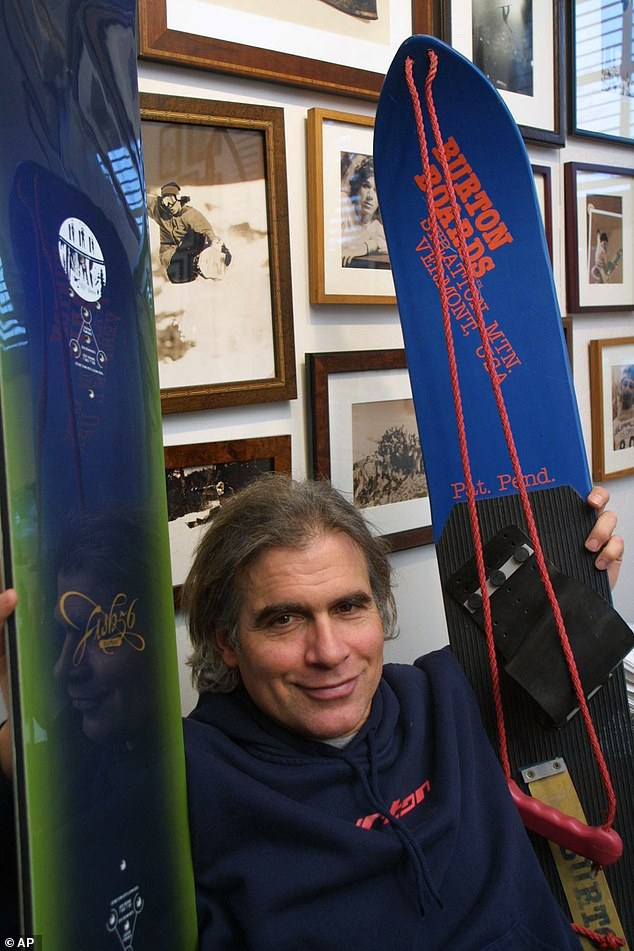 Carpenter is seen above showing off earlier models of his snowboards in March 2002