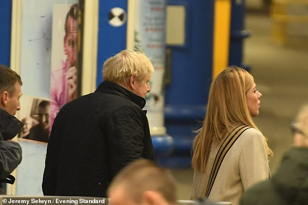 Boris Johnson with partner Carrie Symonds prepare to board a train to Manchester for the debate this morning
