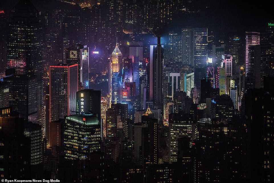 The Hong Kong skyline at night, 2018. A luminescent blue hue surrounds billboards shining from the top of a skyscraper