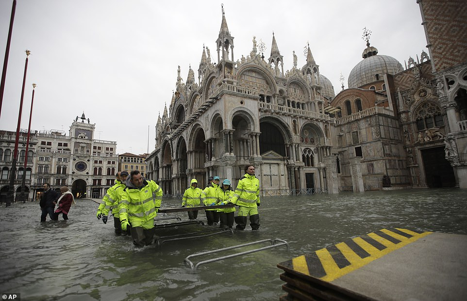 Recovery: Workers in Venice carry wooden boards to create a bridge across St Mark's Square today, with the plaza still submerged three days after the peak of the floods with further misery on the way today