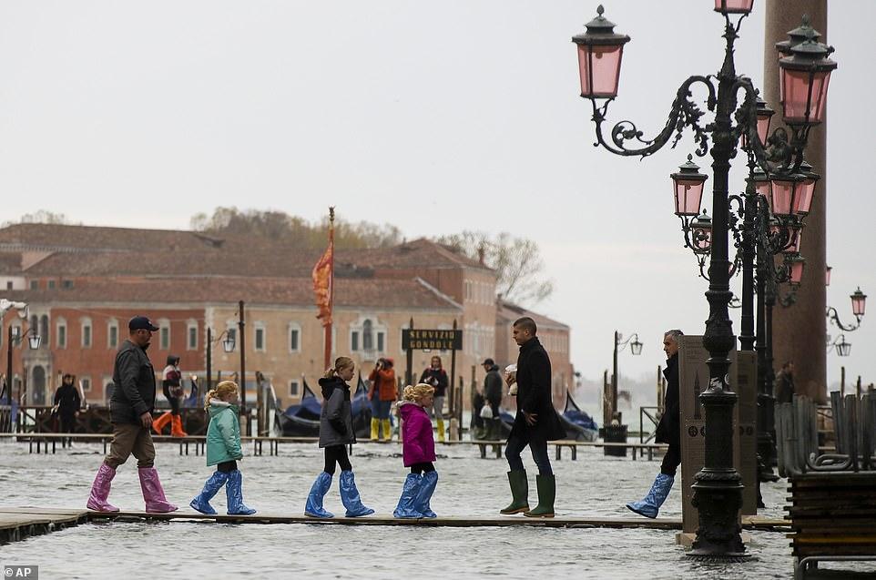 Walkway: People wearing colourful waterproof overshoes walk across a temporary bridge in Venice today
