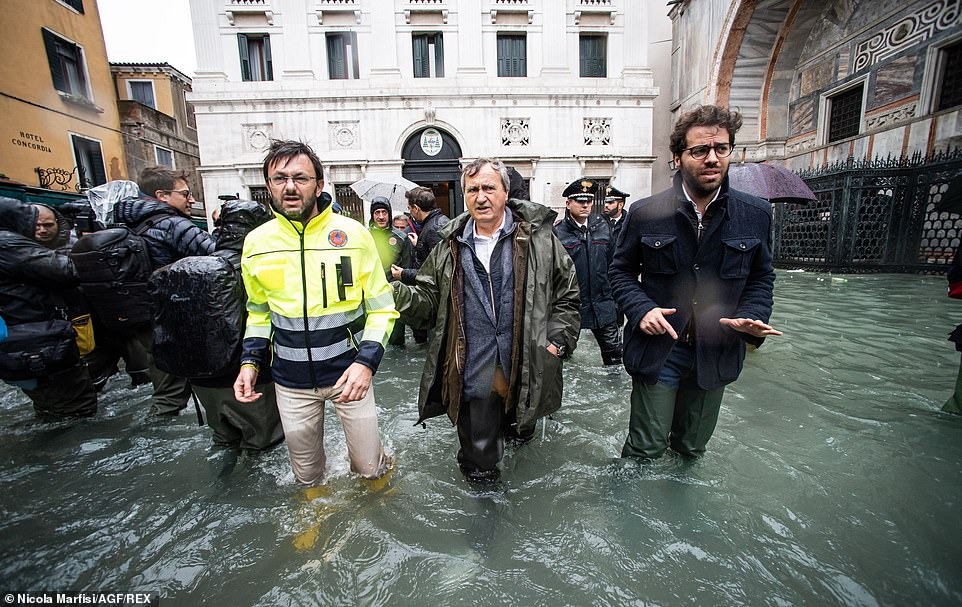 Venice mayor Luigi Brugnaro (centre) inspects the latest flood damage, with water reaching up to his knees on Friday