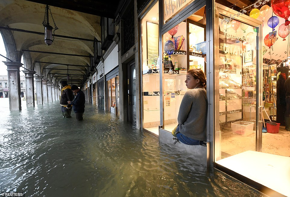 A woman sits in a shop window today while another two men stand knee-deep in water on the fringes of St Mark's Square