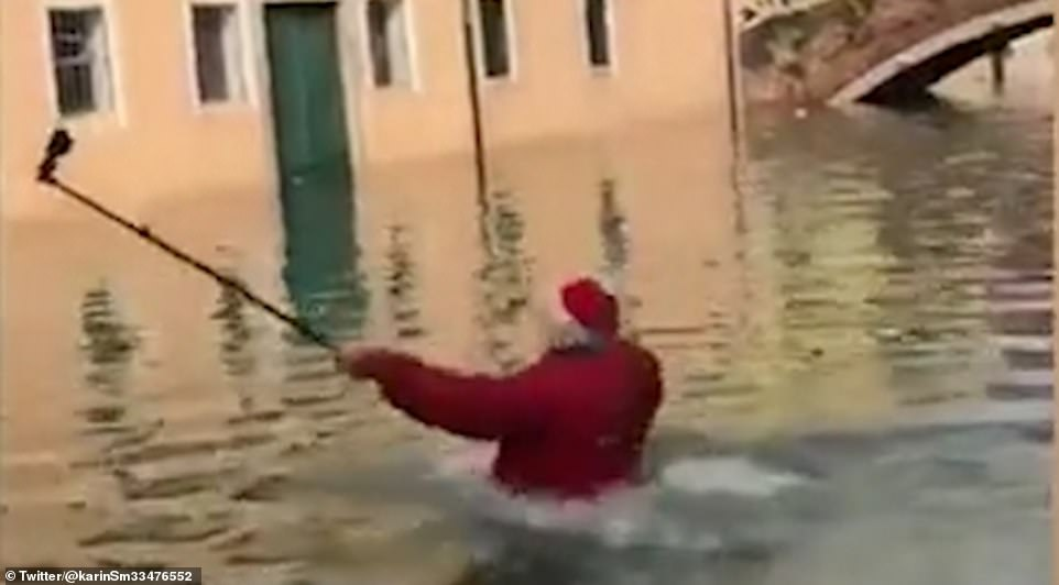 As he fell up to his neck in the high tide, the Santa hat-wearing man called out to his friend who was in safety on higher ground, before slowly making his way back to the shallower water covering the street