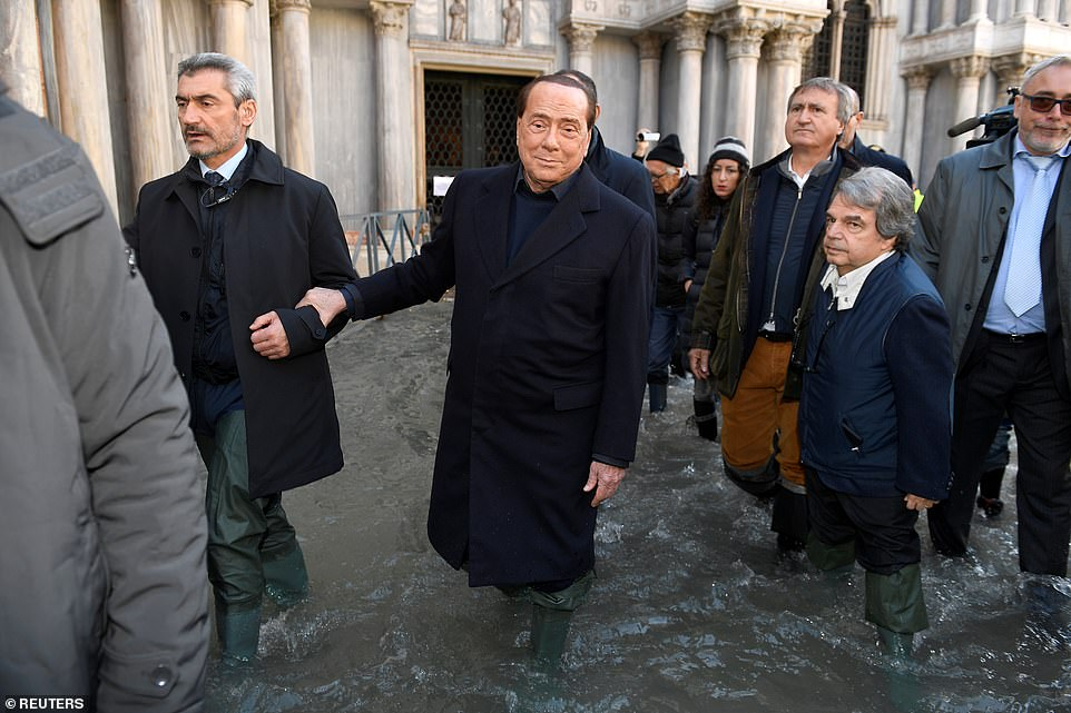 Visitor: Former Italian premier Silvio Berlusconi walks through the flooded St Mark's Square on a visit to the city yesterday