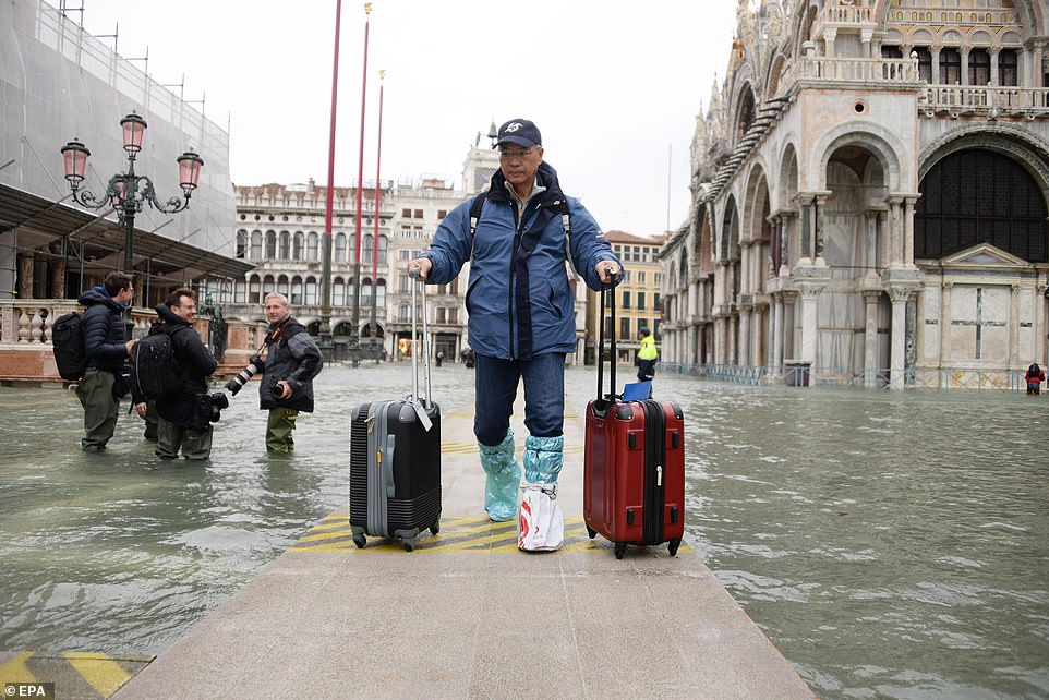 A tourist navigates a platform near St Mark's Basilica holding two suitcases, with a group of photographers nearby