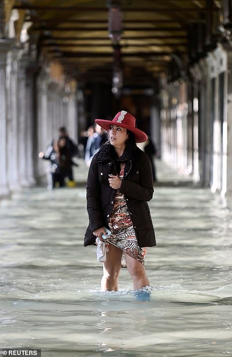 A woman wades in knee-deep water at the flooded St. Mark's Square yesterday