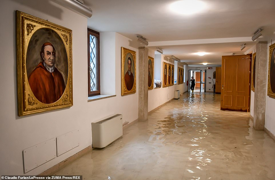 A corridor full of wall paintings is partly flooded in Venice today as the high waters returned just days after Tuesday's devastation