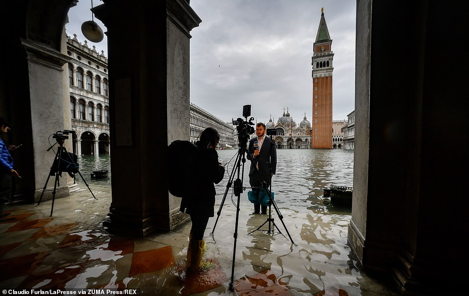 On the scene: A journalist delivers a news report from St Mark's Square which was closed off to tourists on Friday