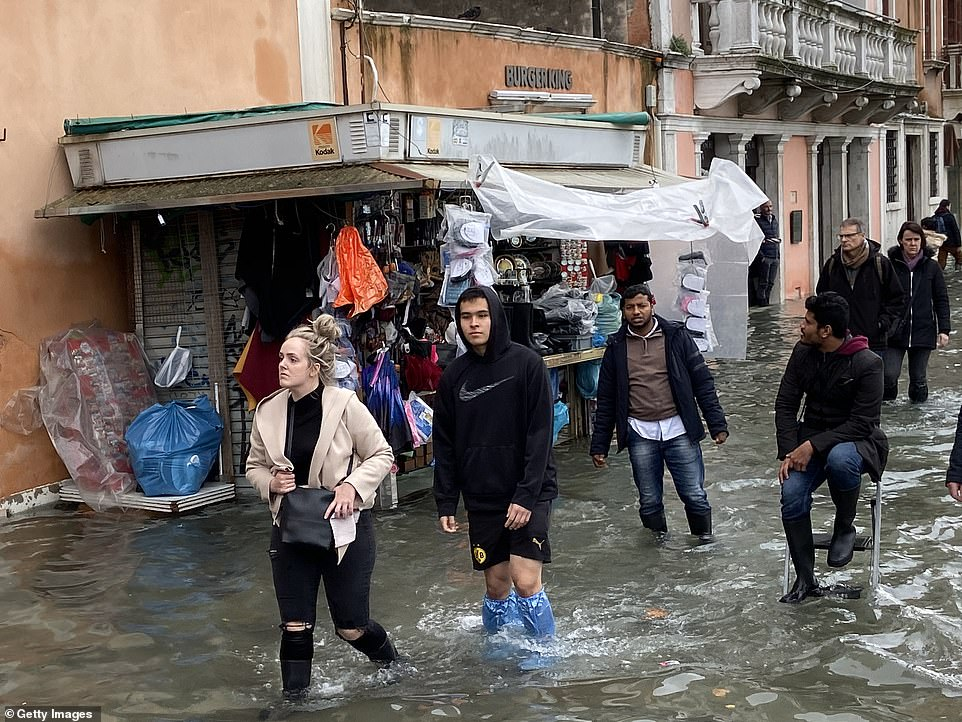 People walk through the high water in Venice today as the tide reached five feet again, causing significant disruption