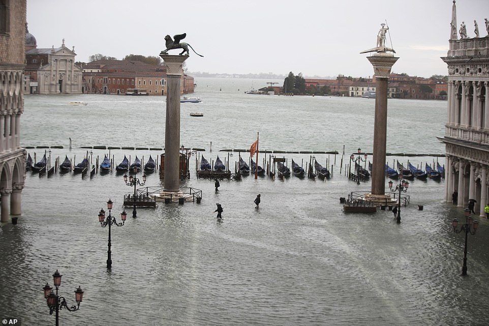 A row of gondolas lines the edge of what is normally St Mark's Square, with a few people seen wading through the water today