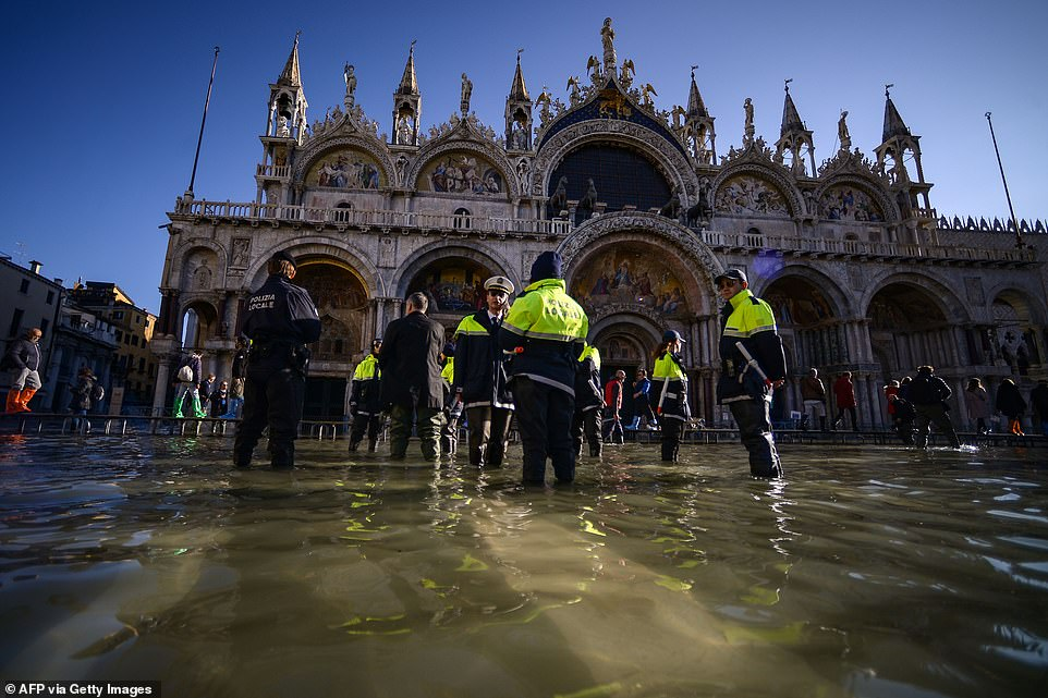 Members of the municipal police stand by St. Mark's Basilica on the the flooded St. Mark's Square yesterday
