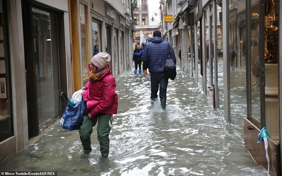 People wade through the water in an alleyway in Venice yesterday with Italy's government declaring a state of emergency