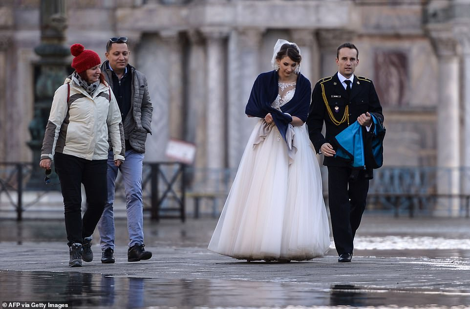 Just married: A newlywed couple walk across a flooded square yesterday as Italy declared a state of emergency
