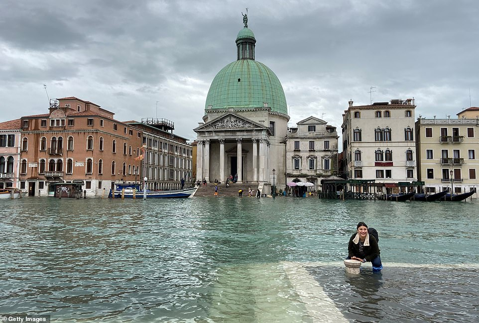 Submerged a second time: A woman wades in floodwaters on a Venetian canal today after water levels rose to five feet for the second time in days and brought further misery to the Italian city