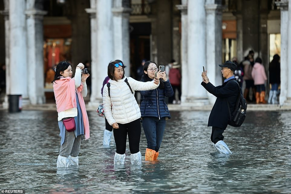 People take pictures in the flooded St Mark's Square yesterday as water levels remained high two days after the floods