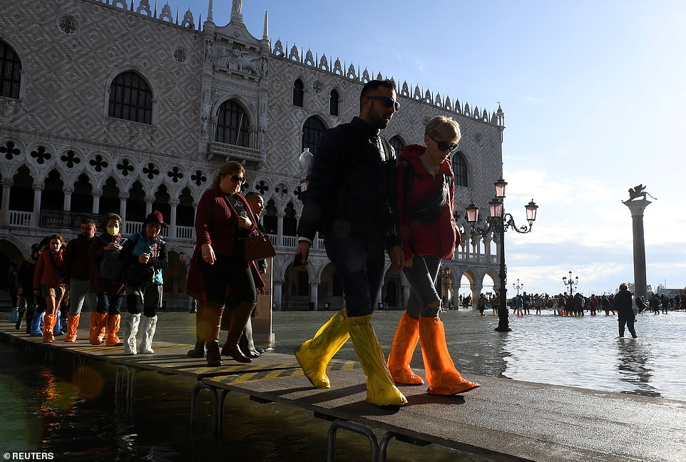 People in protective footwear walk along a temporary platform to cross part of St Mark's Square on Thursday