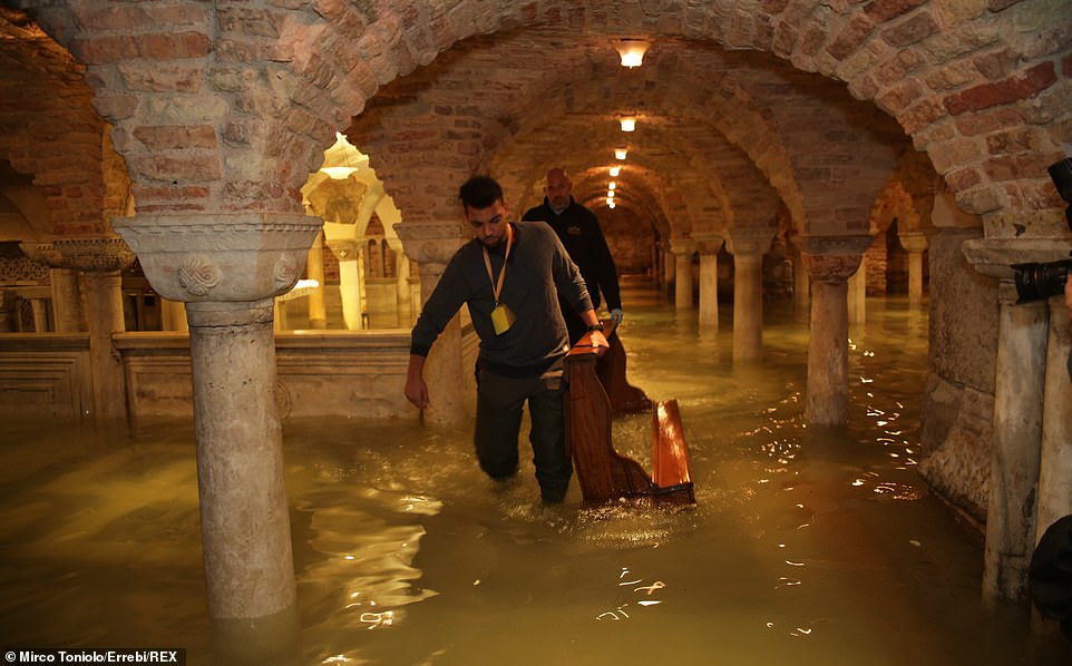 Two people carry a piece of wooden furniture out of the flooded crypt of St Mark's Basilica where major damage is feared