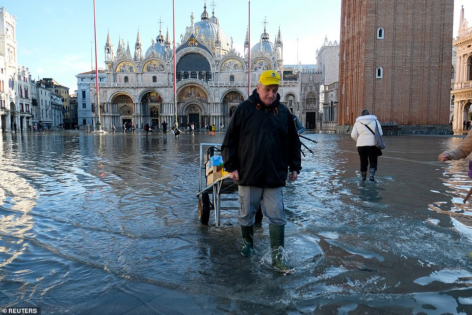 Still flooded: A man pulls a cart through St Mark's Square yesterday morning, where waters have receded from their peak but where much of the plaza is still submerged and the historic St Mark's Basilica in the background has been partially flooded