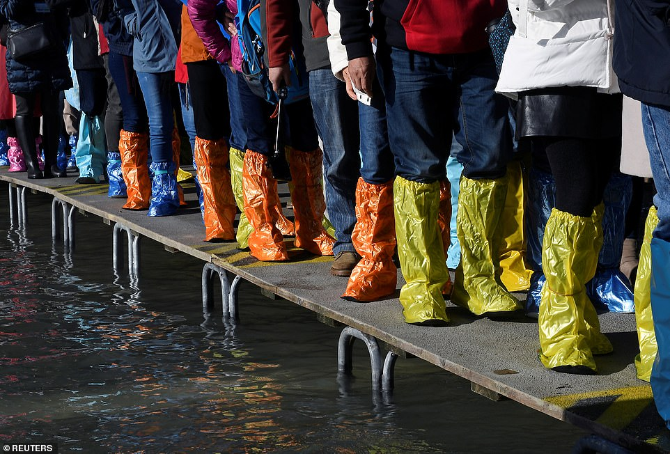 People wearing yellow and orange waterproof footwear walk along a temporary platform near the flooded St Mark's Square