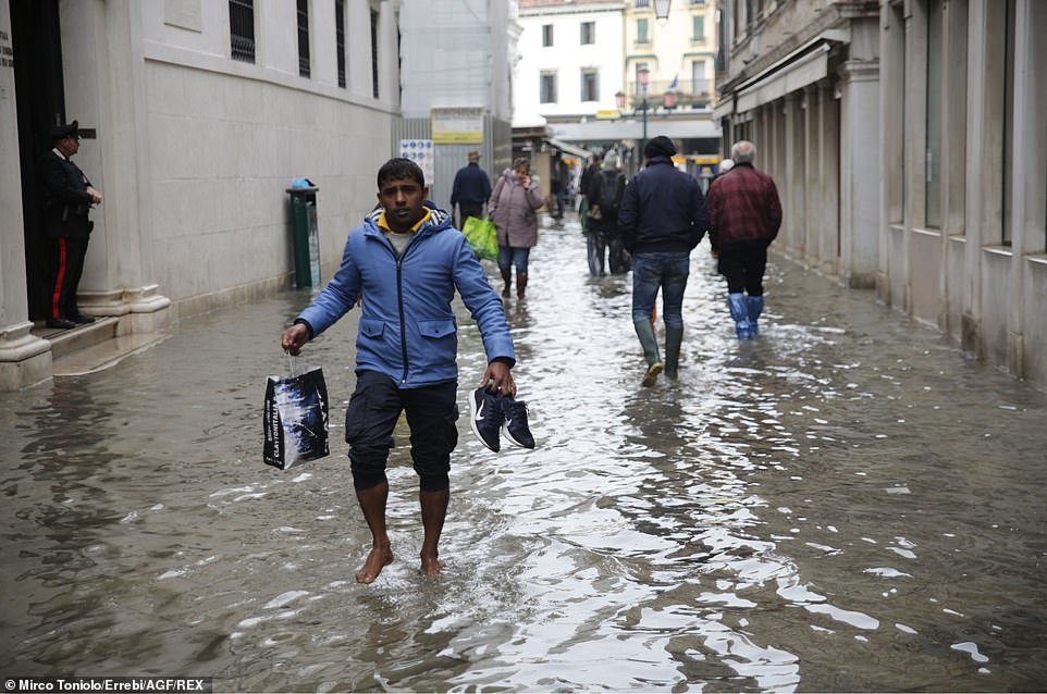 A man holds his shoes as he wades barefoot through water after flooding which was described as 'apocalyptic'