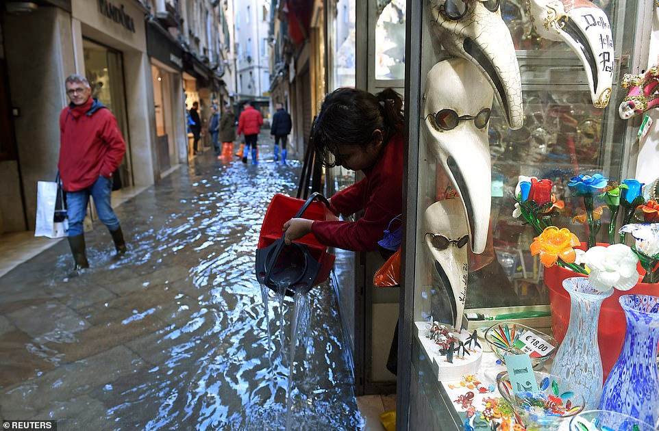 A woman with a bucket slops water out of her shop in a Venice alleyway as another man wearing boots looks on