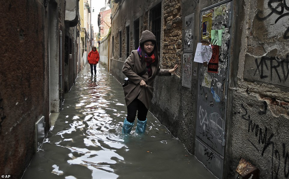 A woman wearing blue protective footwear steadies herself by the side of a flooded alleyway in Venice