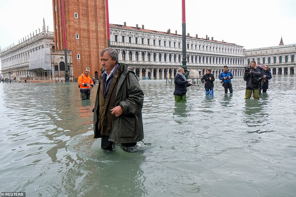 Wading in the water: The mayor of Venice, Luigi Brugnaro, walks in the submerged St Mark's Square yesterday as Venice responds to one of the worst episodes of flooding in its history - which the mayor has blamed on climate change