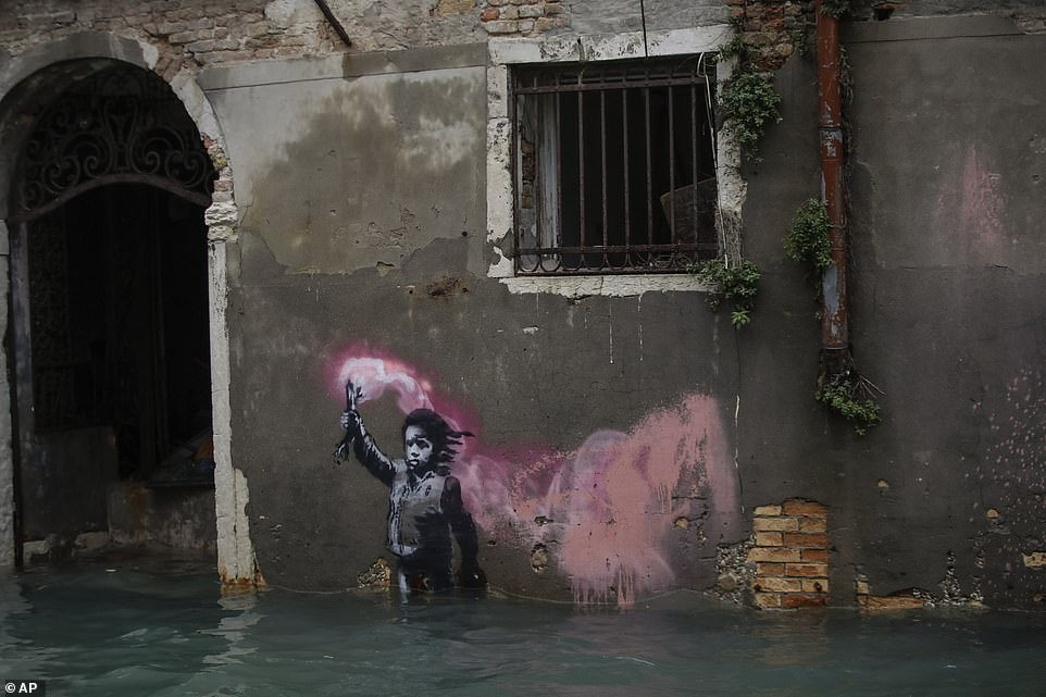 Banksy's migrant child mural is partially submerged for the second time in a week during the latest flooding in Venice today