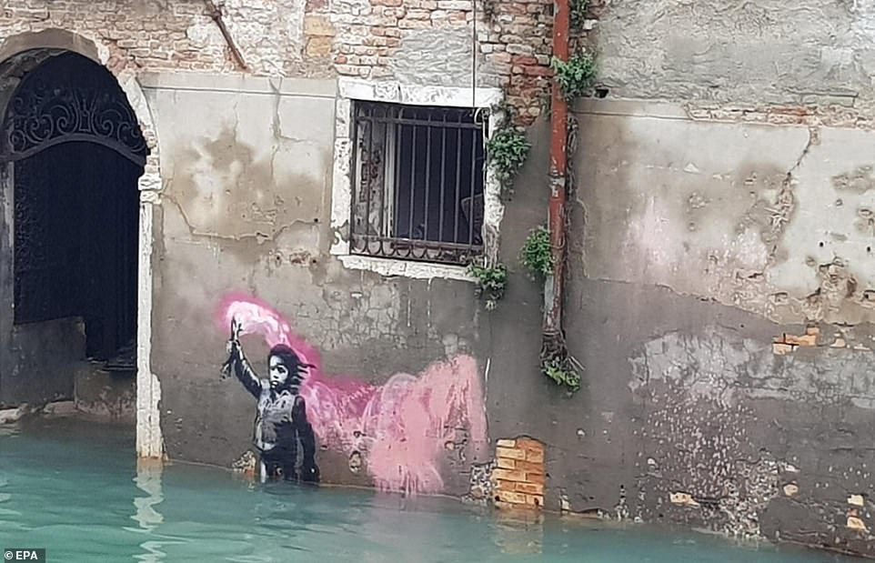 A Banksy artwork of a migrant child is seen partially submerged by the floodwater in Venice on Wednesday