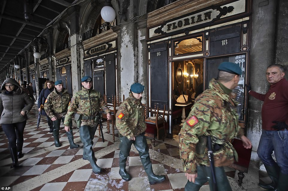 Italian soldiers walk past a flooded cafe by the side of St Mark's Square as they help the clean-up operation in Venice