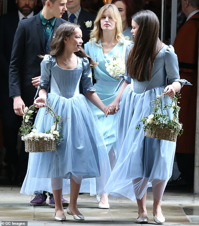 All in blue: The two teenagers were flower girls, while Georgia, a bridesmaid, walked her mom down the aisle