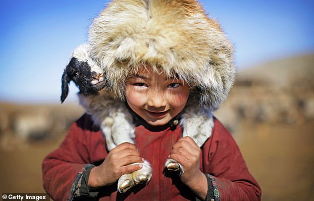 Back in time: A Mongolian boy carries a lamb
