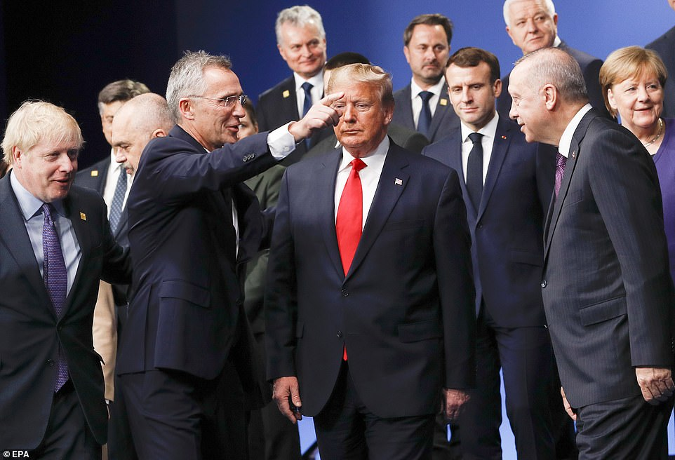 Trump does not look happy as other leaders surround him smiling trying to pose for a group photograph at the summit