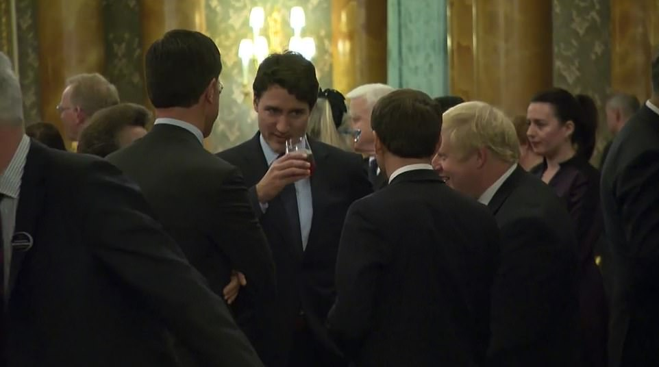 Trudeau swigs from his drink and gestures towards the French President as if he is passing the baton' to Macron to give his take on the situation