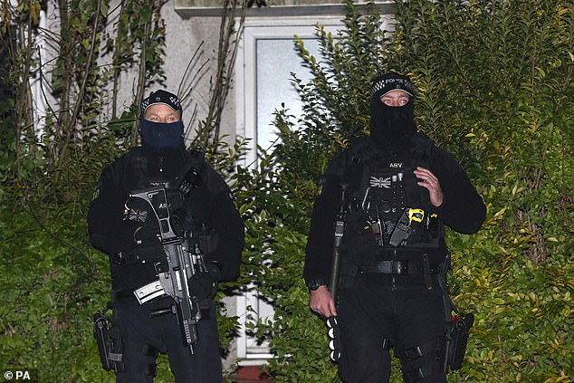 Armed police stand guard outside a house in Loughton believed to belong to the suspect