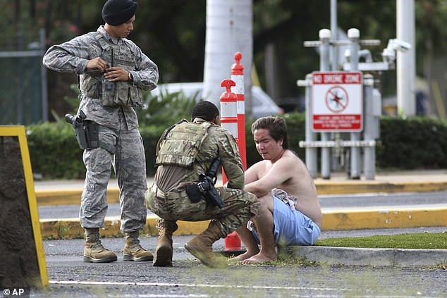 Security forces attend to an unidentified male outside the the main gate at Joint Base Pearl Harbor-Hickam, Wednesday, following a shooting which killed two civilians